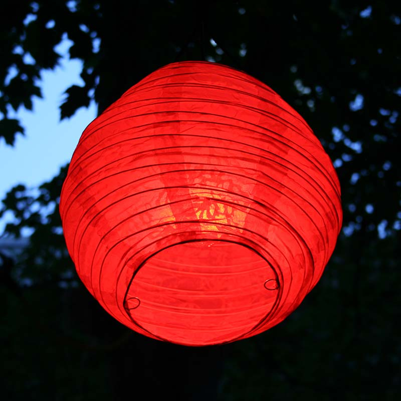 A red paper Chinese lantern hanging in a park.