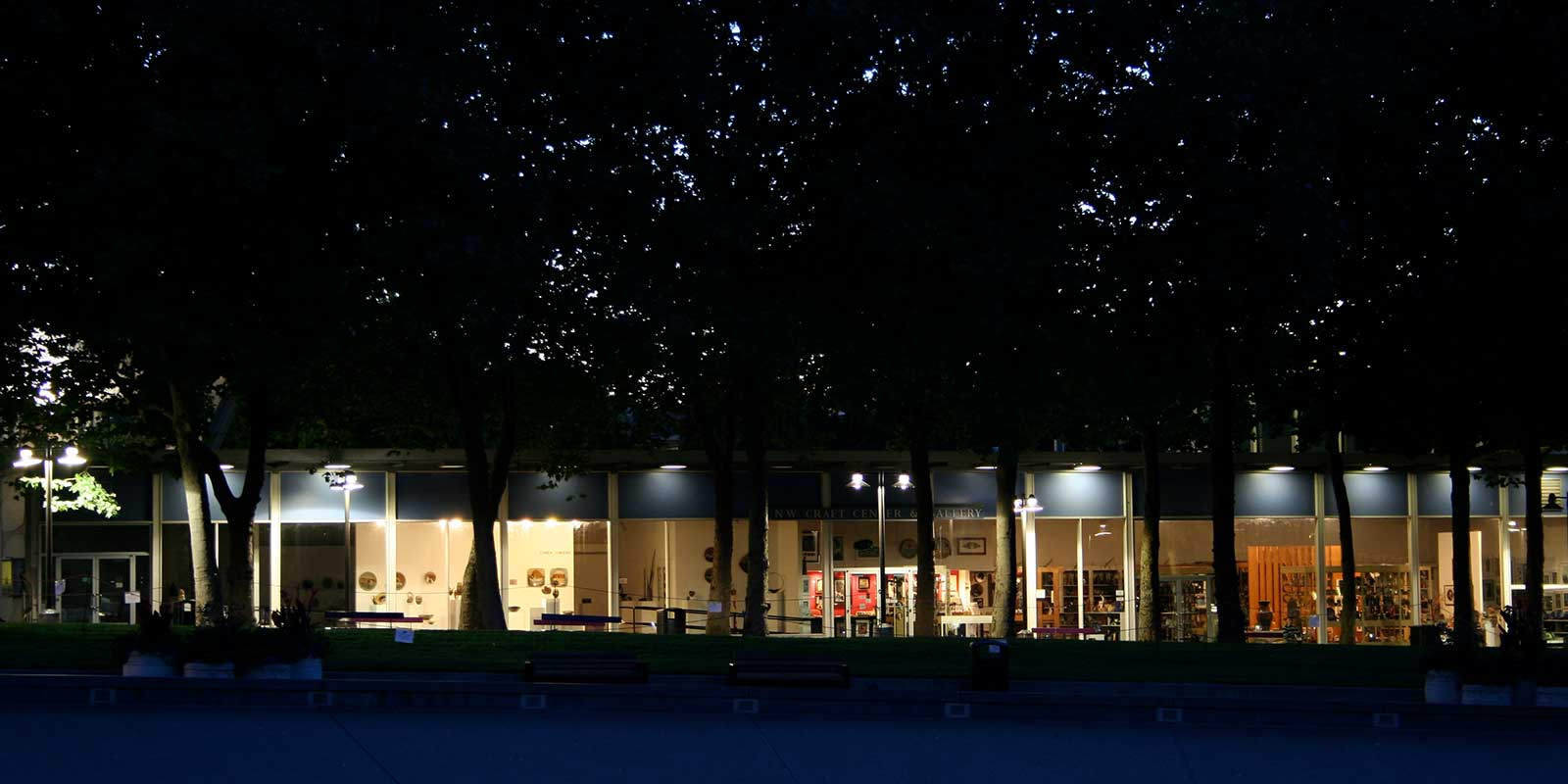 A dimly lit row of windows under trees showing artwork at Seattle Center.